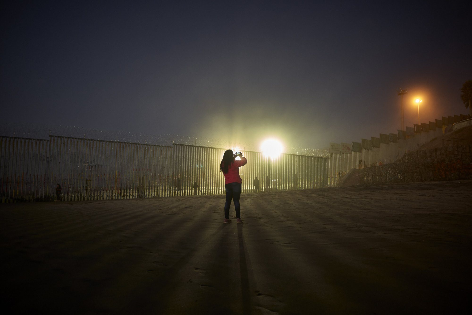 FILE - In this Jan. 10, 2019, file photo, a woman records with her phone, as floodlights from the United States light up the border wall, topped with razor wire along the beach in Tijuana, Mexico. The government is working on replacing and adding fencing in various locations, and Trump in February declared a national emergency to get more funding for the wall. (AP Photo/Gregory Bull, File)