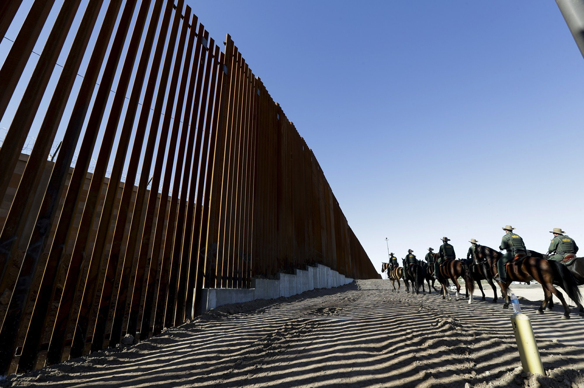 In this Oct. 26, 2018, file photo, mounted Border Patrol agents ride along a newly fortified border wall structure in Calexico, Calif. (AP Photo/Gregory Bull, File)