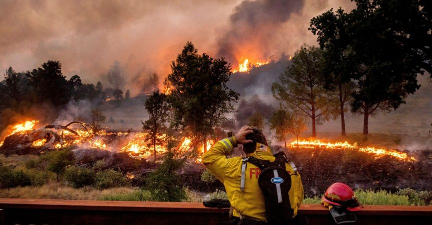 FILE - In this Aug. 21, 2020, file photo, a firefighter rubs his head while watching the LNU Lightning Complex fires spread through the Berryessa Estates neighborhood of unincorporated Napa County, Calif. Deadly wildfires in California have burned more than 4 million acres (6,250 square miles) this year — more than double the previous record for the most land burned in a single year in the state. California fire officials said the state hit the astonishing milestone Sunday, Oct. 4, 2020 with about two months remaining in the fire season. (AP Photo/Noah Berger, File)