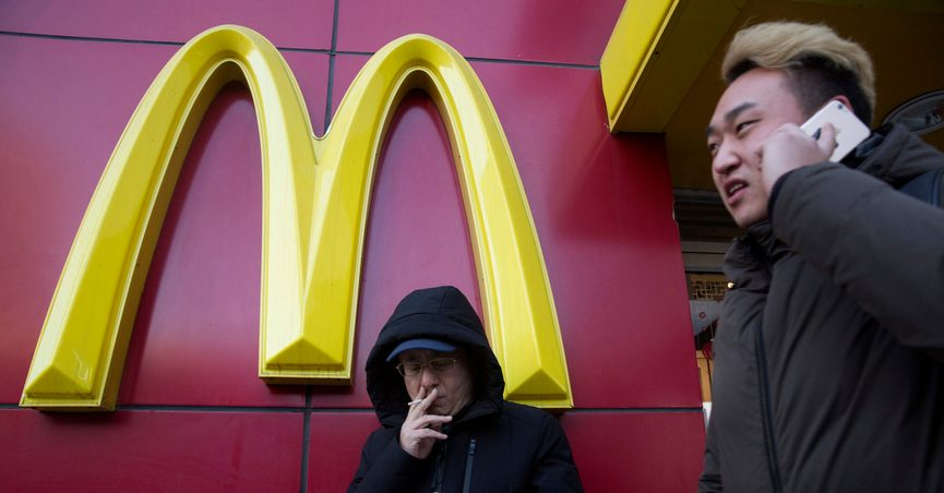 FILE - In this Jan. 10, 2017, file photo, a man smokes outside a McDonald's restaurant in Beijing, China. McDonald's is selling a sandwich made of Spam topped with crushed Oreo cookies Monday, Dec. 21, 2020 in China in an attention-grabbing move that has raised eyebrows. (AP Photo/Ng Han Guan, File)
