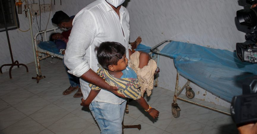 A young patient is carried by a man at the district government hospital in Eluru, Andhra Pradesh state, India, Monday, Dec.7, 2020. Health officials and experts are still baffled by a mysterious illness that has left over 500 people hospitalized and one person dead in this southern Indian state. (AP Photo)