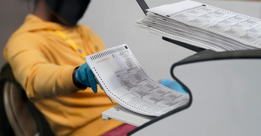 FILE - In this Nov. 5, 2020, file photo, a county election worker scans mail-in ballots at a tabulating area at the Clark County Election Department in Las Vegas. (AP Photo/John Locher, File)