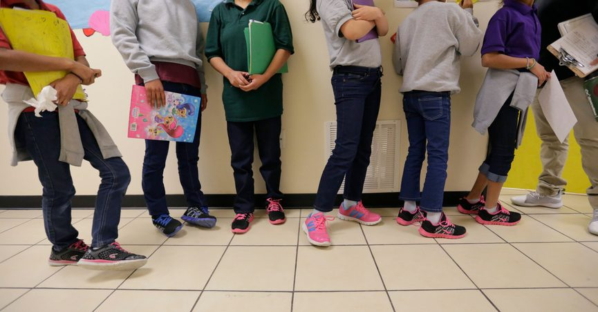 """FILE - In this Aug. 29, 2019, file photo, migrant teens line up for a class at a """"tender-age"""" facility for babies, children and teens, in Texas' Rio Grande Valley, in San Benito, Texas. With its long-term facilities for immigrant children nearly full, the Biden administration is working to expedite the release of children to their relatives in the U.S. The U.S. Health and Human Services on Wednesday, Feb. 24, 2021, authorized operators of long-term facilities to pay for some of the children's flights and transportation to the homes of their sponsors. (AP Photo/Eric Gay File)"""
