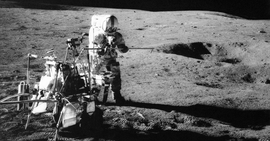 """FILE - In this Feb. 6, 1971, file photo, Apollo 14 astronaut Alan B. Shepard Jr. conducts an experiment near a lunar crater using an instrument from a two-wheeled cart carrying various test tools. Apollo 14 commander Alan B. Shepard Jr. and his crew brought back 42 kilograms of moon rocks. Left behind were two golf balls that Shepard, who later described the moon's surface as """"one big sand trap,"""" hit with a makeshift 6-iron to become a footnote in history. (NASA via AP, File)"""