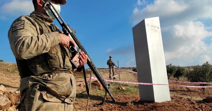 """Turkish police officers guard a monolith, found on an open field near Sanliurfa, southeastern Turkey, Sunday, Feb. 7, 2021. The metal block was found by a farmer Friday in Sanliurfa province with old Turkic script that reads """"Look at the sky, see the moon."""" The monolith that mysteriously appeared and disappeared on a field in southeast Turkey has turned out to be a publicity gimmick ahead of a government event during which Turkish President Recep Tayyip Erdogan announced a space program for the country. (Bekir Seyhanli/IHA via AP)"""