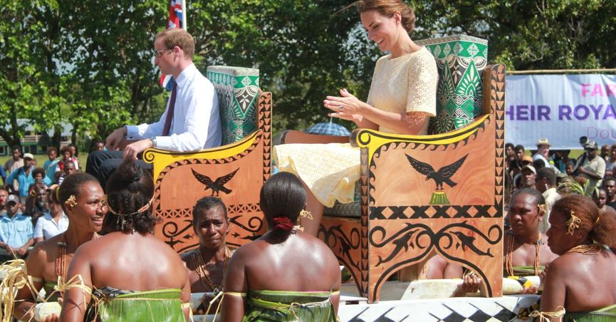 Prince William and Kate are carried on portable thrones or litters.