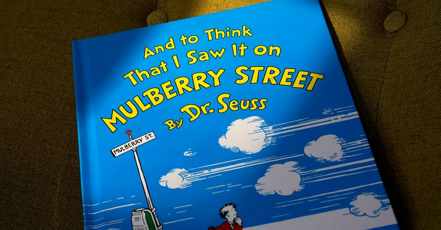 """A copy of the book """"And to Think That I Saw It on Mulberry Street,"""" by Dr. Seuss, rests in a chair, Monday, March 1, 2021, in Walpole, Mass. Dr. Seuss Enterprises, the business that preserves and protects the author and illustrator's legacy, announced on his birthday, Tuesday, March 2, 2021, that it would cease publication of several children's titles including """"And to Think That I Saw It on Mulberry Street"""" and """"If I Ran the Zoo,"""" because of insensitive and racist imagery. (AP Photo/Steven Senne)"""