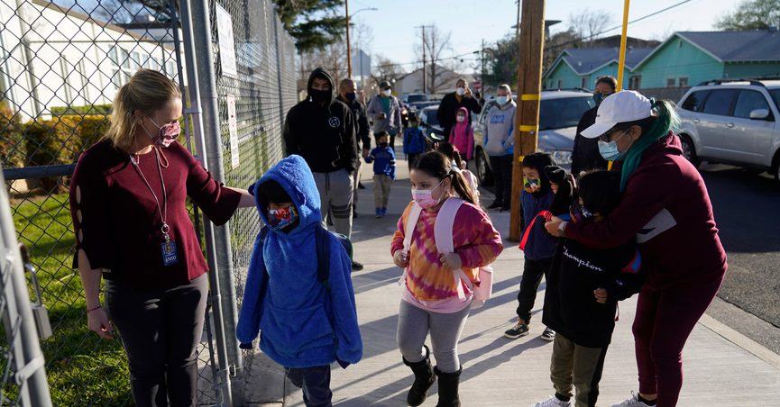 FILE - In this Feb. 25, 2021, file photo, Assistant Principal Janette Van Gelderen, left, welcomes students at Newhall Elementary in Santa Clarita, Calif. California's public schools could get $6.6 billion from the state Legislature if they return to in-person instruction by the end of March, according to a new agreement announced Monday, March 1, 2021, between Gov. Gavin Newsom and the state's legislative leaders. (AP Photo/Marcio Jose Sanchez, File)