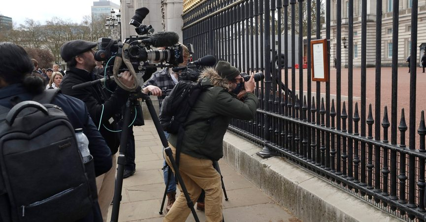 FILE - In this Friday, April 9, 2021 file photo, members of the media take images of an announcement, regarding the death of Britain's Prince Philip, displayed on the fence of Buckingham Palace in London. When Prince Philip's death was announced, the BBC switched instantly into mourning mode. Regular programming on the U.K.'s national broadcaster was canceled for special coverage, hosted by black-clad news anchors. Some Britons felt it a fitting mark of respect, but for others it was a bit much. (AP Photo/Matt Dunham, File)