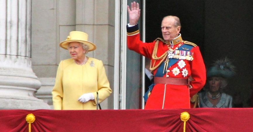 """A photo shows Queen Elizabeth laughing after Prince Philip """"pranked"""" her by disguising himself as a palace guard."""