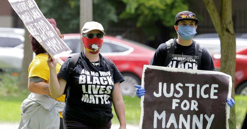 """FILE - A protester holds a sign that reads """"Justice for Manny"""" in this June 5, 2020 file photo in Tacoma, Wash., during a protest against police brutality. On Thursday, May 27, 2021, the Washington state attorney general filed criminal charges against three police officers in the death of Manuel Ellis, a Black man who died after telling the Tacoma officers who were restraining him he couldn't breathe. (AP Photo/Ted S. Warren, File)"""