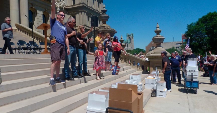 """FILE - In this June 17, 2021 file photo, conservatives gather on the steps of the Michigan Capitol before delivering thousands of affidavits requesting that lawmakers order an """"forensic"""" audit of the 2020 election in Lansing, Mich. Senate Republicans who investigated Michigan's presidential election say there was no widespread or systemic fraud in a report Wednesday, June 23, 2021. (AP Photo/David Eggert File)"""