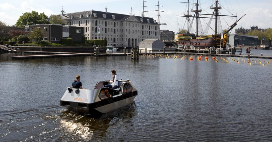 An electric boat steers close to a full-size replica of the 18th century three-mast trading ship Amsterdam at the National Maritime Museum, in Amsterdam, Thursday, May 20, 2021. Already steeped in maritime history, the city's more than 100 kilometers (60 miles) of waterways are to start hosting prototypes of futuristic boats — small, fully-autonomous electric vessels — to carry out tasks including transporting passengers and picking up garbage. (AP Photo/Peter Dejong)