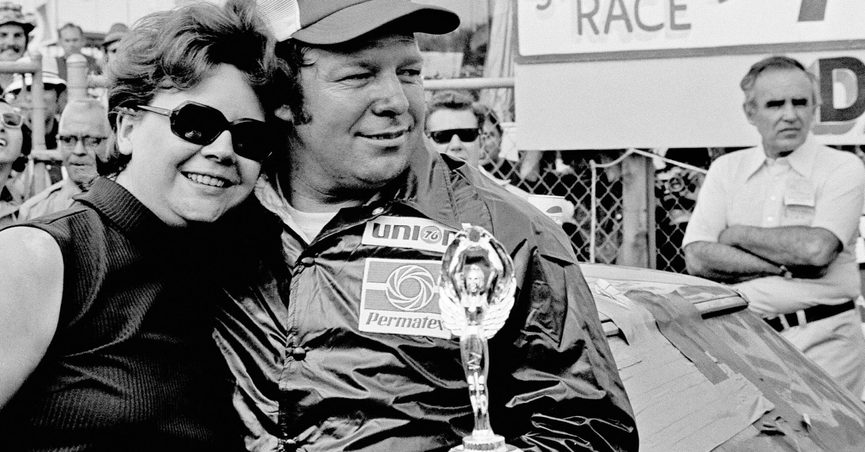 FILE - In this Feb. 15, 1975, file photo, Jack Ingram gives his wife, Aline, a big hug after accepting the trophy from his victory in the Permatex 300 auto race at Daytona International Speedway in Daytona Beach, Fla. Ingram, a hard-hosed, hot-tempered racer who won five NASCAR championships and more than 300 races, has died, the NASCAR Hall of Fame said Friday, June 25, 2021. He was 84. (AP Photo/File)