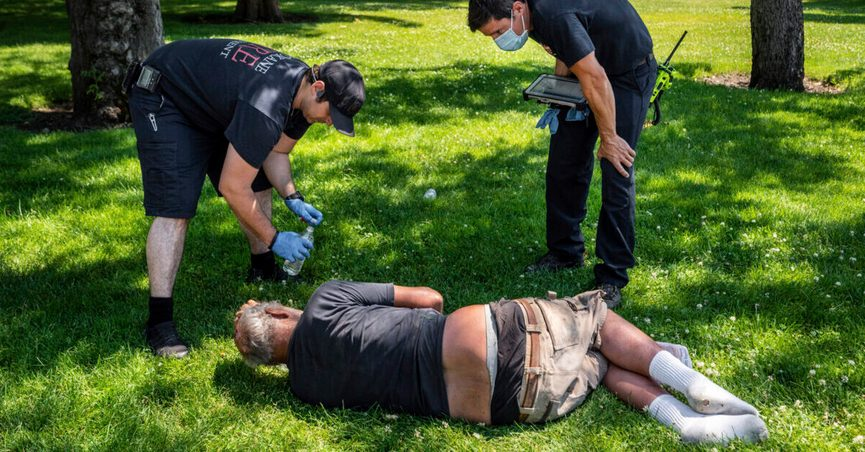 With the temperature well over 100 degrees, Spokane, Wash., firefighter Sean Condon, left and Lt. Gabe Mills, assigned to the Alternative Response Unit of of Station 1, check on the welfare of a man in Mission Park in Spokane, Wash., Tuesday, June 29, 2021. The special fire unit, which responds to low priority calls, has been kept busy during this week's heatwave. (Colin Mulvany/The Spokesman-Review via AP)