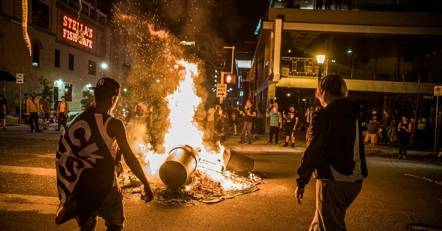Protesters set a dumpster on fire after a shooting on Thursday, June 3, 2021 in Minneapolis. Crowds vandalized buildings and stole from businesses in Minneapolis' Uptown neighborhood after officials said a man wanted for illegally possessing a gun was fatally shot by authorities. (Richard.Tsong-Taatari/Star Tribune via AP)