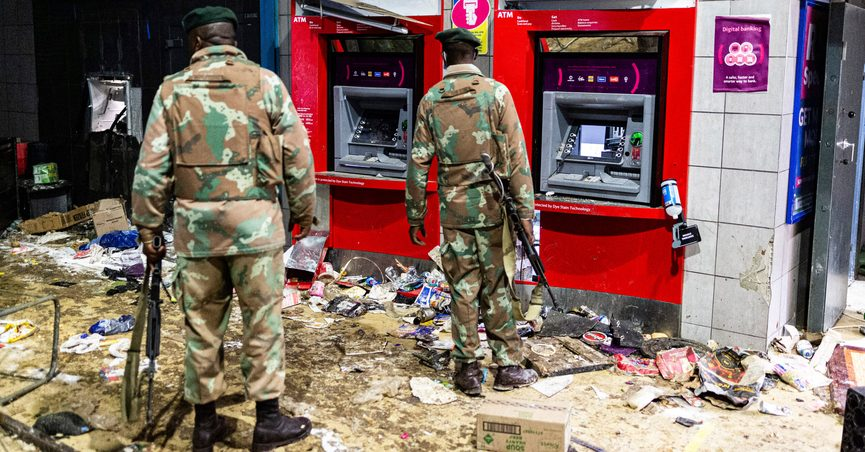 Soldiers guard an autobahn at the Bara taxi rank shops in Soweto, Johannesburg, Monday, July 12, 2021. Police say six people are dead and more than 200 have been arrested amid escalating violence during rioting that broke out following the imprisonment of South Africa's former President Jacob Zuma. (AP Photo/Ali Greeff)