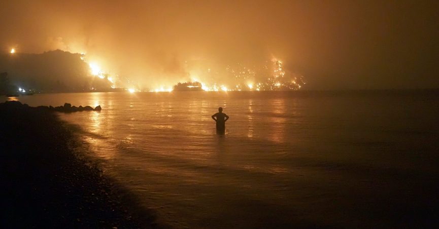 A man watches the flames as wildfire approaches Kochyli beach near Limni village on the island of Evia, about 160 kilometers (100 miles) north of Athens, Greece, late Friday, Aug. 6, 2021. Wildfires raged uncontrolled through Greece and Turkey for yet another day Friday, forcing thousands to flee by land and sea, and killing a volunteer firefighter on the fringes of Athens in a huge forest blaze that threatened the Greek capital's most important national park. (AP Photo/Thodoris Nikolaou)