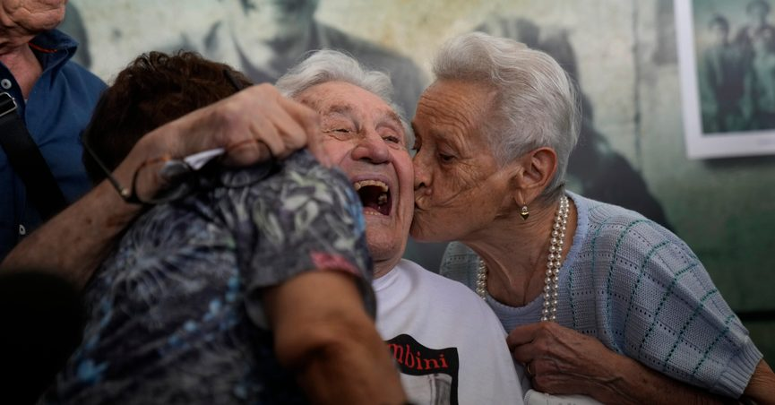Martin Adler, a 97-year-old retired American soldier, center, receives a kiss from Mafalda, right, and Giuliana Naldi, whom he saved during WWII, during a reunion at Bologna's airport, in Italy, Monday, Aug. 23, 2021. For more than seven decades, Adler treasured a black-and-white photo of himself as a young soldier with a broad smile with three impeccably dressed Italian children he is credited with saving as the Nazis retreated northward in 1944. The veteran met the three siblings - now octogenarians themselves - in person for the first time on Monday, eight months after a video reunion. (AP Photo/Antonio Calanni)