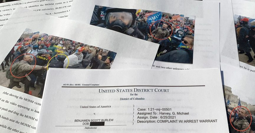 The affidavit in support of a criminal complaint and arrest warrant for Benjamen Scott Burlew is photographed Tuesday, Aug. 24, 2021. Berlew of Miami, Okla., is seen on video pushing Associated Press photographer John Minchillo over a wall outside the Capitol during the Jan. 6 riot. Burlew is the second person to be charged with Minchillo, who was documenting the mob of former President Donald Trump's supporters that day. (AP Photo/Jon Elswick)