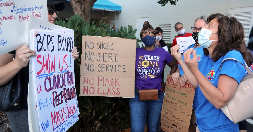 Yvonne Moniz, right, a special needs teacher at Challenger Elementary, along with Oakland Park Elementary third grade teacher Donna Sacco, second from right, and Oriole Elementary fourth grade teacher Yolanda Smith, center, tries to persuade anti-mask protester Heather Tanner that all students need to wear masks to protect the most vulnerable. during a protest outside of a Broward County School Board meeting, Tuesday, Aug. 10, 2021, in in Fort Lauderdale, Fla., to discuss a possible mask mandate when school starts next week. (Amy Beth Bennett/South Florida Sun-Sentinel via AP)