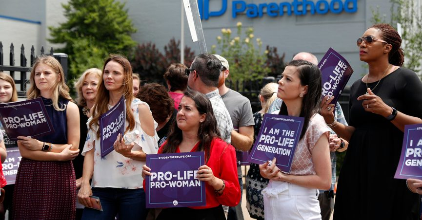 FILE - In this June 4, 2019, file photo, anti-abortion advocates gather outside the Planned Parenthood clinic in St. Louis. A federal appeals court on Tuesday, Sept. 21, 2021, will consider whether Missouri can implement a sweeping law aimed at limiting abortions. The law adopted in 2019 would ban abortions at or around the eighth week of pregnancy. It also would prohibit abortions based on a Down syndrome diagnosis. (AP Photo/Jeff Roberson, File)