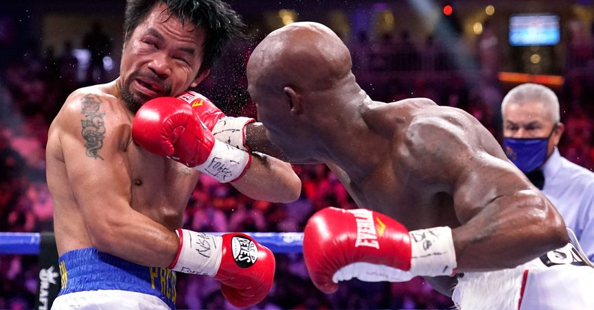 FILE - In this Aug. 21, 2021, file photo, Manny Pacquiao, left, of the Philippines, receives a punch from Yordenis Ugas, of Cuba, in a welterweight championship boxing match in Las Vegas. Boxing legend Pacquiao is officially hanging up his gloves. The eight-division world champion and Philippines senator on Wednesday, Sept. 29, 2021, announced his retirement from the ring, (AP Photo/John Locher, File)