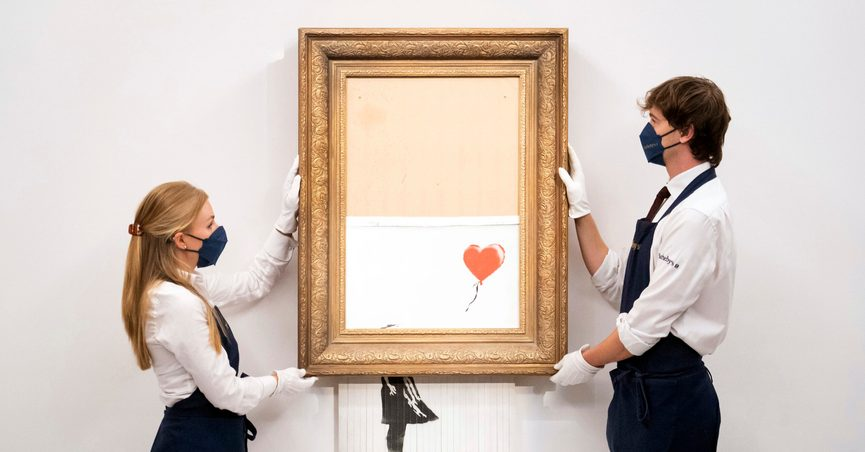 """Art handlers at Sotheby's auction house hold Banksy's 'Love is in the Bin', before it returns to auction at Sotheby's, London, Friday, Sept. 3, 2021. A Banksy artwork that was sensationally shredded just after it sold for $1.4 million us up for sale again -- at several times the price. Sotheby's said Friday that """"Love is in the Bin"""" will be offered at an Oct. 14 auction in London, with a pre-sale estimate of 4 million pounds to 6 million pounds ($5.5 million to $8.3 million). (Dominic Lipinski/PA via AP)"""
