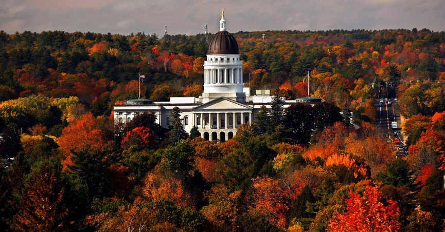 FILE - In this Oct. 23, 2017, file photo, the State House is surrounded by fall foliage in Augusta, Maine. Recent leaf-peeping seasons have been disrupted by weather conditions in New England, New York and elsewhere. Arborists and ecologists say the trend is likely to continue as the planet warms. (AP Photo/Robert F. Bukaty, File)