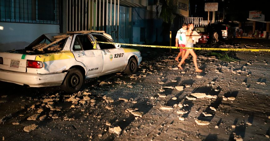 A couple walks past a taxi cab that was damaged by falling debris after a strong earthquake in Acapulco, Mexico, Tuesday, Sept. 7, 2021. The quake struck southern Mexico near the resort of Acapulco, causing buildings to rock and sway in Mexico City nearly 200 miles away. (AP Photo/ Bernardino Hernandez)