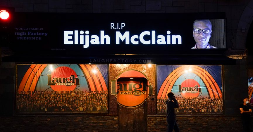 FILE - In this Aug. 24, 2020, file photo, a man walks past a display showing an image of Elijah McClain outside Laugh Factory during a candlelight vigil for McClain in Los Angeles. Colorado's attorney general plans to make an announcement Wednesday, Sept. 1, 2021 about the grand jury investigation into the death of McClain, a Black man who was put in a chokehold and injected with a powerful sedative two years ago in suburban Denver. (AP Photo/Jae C. Hong, File)