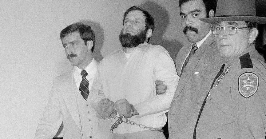 FILE - In this Nov. 23, 1981, file photo, law officials escort a handcuffed David Gilbert, second from left, from Rockland County Court in New City, N.Y. Former Weather Underground radical David Gilbert has been granted parole after decades in prison for his role in a fatal 1981 Brink's robbery north of New York City, a corrections department spokesperson said Tuesday, Oct. 26, 2021. (AP Photo/David Handschuh, File)