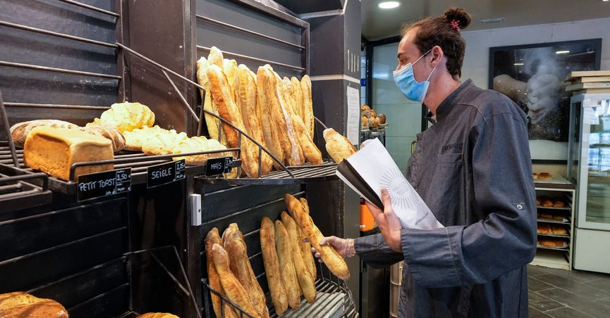 Baker Hugo Hardy prepares baguettes to be sold at Bigot bakery in Versailles, west of Paris, Tuesday, Oct. 26, 2021. A worldwide increase in wheat prices after bad harvests in Russia is forcing French bakers to raise the price of that staple of life in France the baguette. Boulangeries around France have begun putting up signs warning their customers of an increase in the price of their favorite bread due to rising costs. (AP Photo/Michel Euler