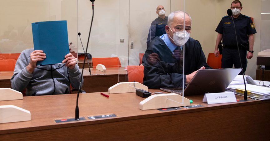 A man accused of murder by omission, left, sits in the courtroom with his lawyer Peter Schnelle before his trial begins, in Munich, Germany. Thursday, Oct. 28, 2021. A German electrician went on trial Thursday accused of murder in the death of one man and mutilating several others by performing illegal operations on their genitals. The 66-year-old told a regional court in Munich that he performed the procedures at the men's request. (Sven Hoppe/dpa via AP)