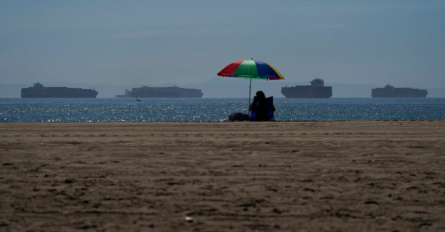A beach goer sits on the beach in Seal Beach Calif., Friday, Oct. 1, 2021, as container ships waiting to dock at the Ports of Los Angeles and Long Beach are seen in the distance. With three months until Christmas, toy companies are racing to get their toys onto store shelves as they face a severe supply network crunch. Toy makers are feverishly trying to find containers to ship their goods while searching for new alternative routes and ports. (AP Photo/Jae C. Hong)