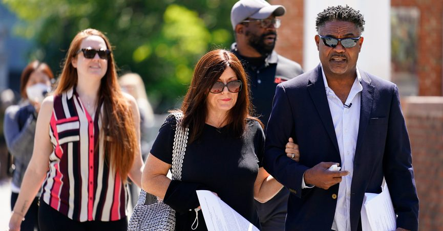 FILE - In this May 14, 2021, file photo, former NFL players Ken Jenkins, right, and Clarence Vaughn III, center right, along with their wives, Amy Lewis, center, and Brooke Vaughn, left, carry petitions demanding equal treatment for everyone involved in the settlement of concussion claims against the NFL, to the federal courthouse in Philadelphia, in this Friday, May 14, 2021, file photo. Lawyers for the NFL and retired players filed proposed changes to the $1 billion concussion settlement on Wednesday, Oct. 20, 2021, to remove race-norming in dementia testing, which made it more difficult for Black players to qualify for payments. (AP Photo/Matt Rourke, File)