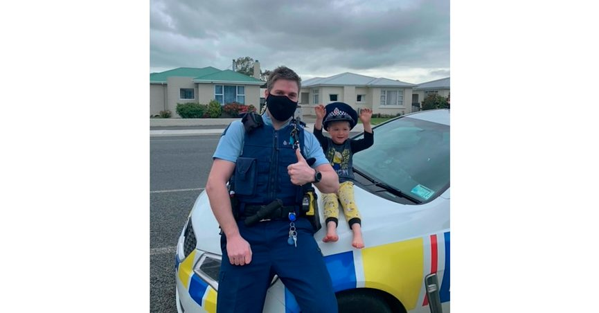 In this photo released by New Zealand Police, an officer identified only as Constable Kurt sits on his patrol car with a 4-year-old boy who is not identified, in the South Island city of Invercargill, New Zealand, Friday, Oct. 15, 2021. An emergency call made by the 4-year-old New Zealand boy asking for police to come over and check out his toys prompted a real-life callout and confirmation from an officer that the toys were, indeed, pretty cool. (NZ Police via AP)