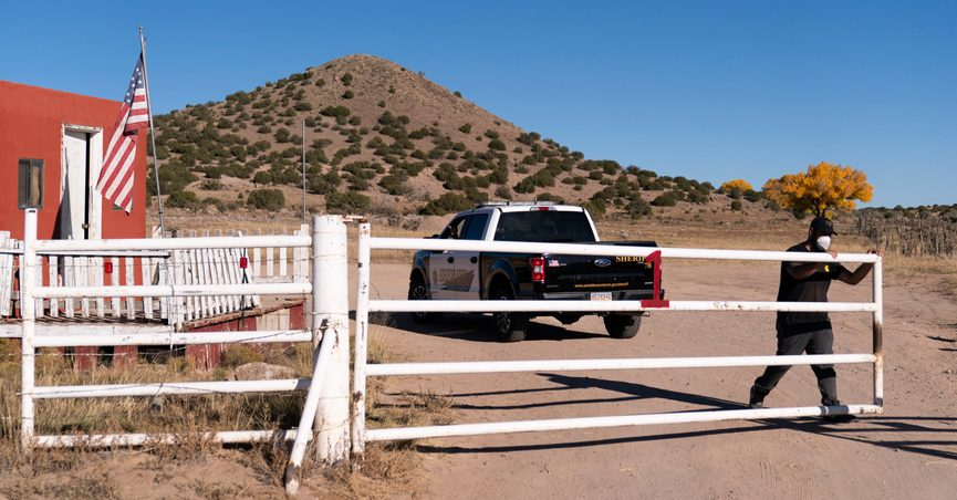"""A security guard closes the gate after a Santa Fe County Sheriff's vehicle entered the Bonanza Creek Ranch in Santa Fe, N.M., Monday, Oct. 25, 2021. Production of the movie that Alec Baldwin was making when he shot and killed a cinematographer last week has been officially halted, but producers of the Western described the move as """"a pause rather than an end."""" (AP Photo/Jae C. Hong)"""