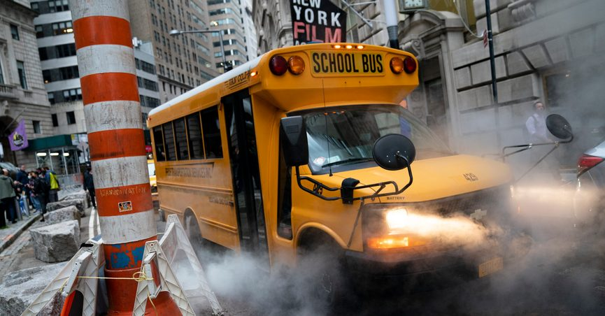 A school bus passes through a steam vent on a morning route, Monday, Oct. 4, 2021, in the Manhattan borough of New York. (AP Photo/John Minchillo)